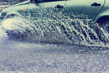 58914232-motion-car-rain-big-puddle-of-water-spray-from-the-wheels